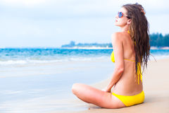 Youn long haired woman in yellow bikini and. Sunglasses sitting on the beach. This image has attached release royalty free stock image