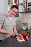 Youn man cutting carrots Royalty Free Stock Photos