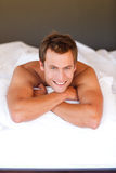 Youn man relaxing in bed Stock Images