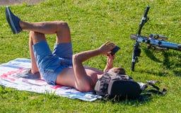 Youn Man Sunbathing Looking en el teléfono móvil Imágenes de archivo libres de regalías