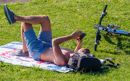 Youn Man Sunbathing Looking no telefone celular Imagens de Stock Royalty Free
