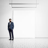 Youn man wearing suit and blank poster on a wall Royalty Free Stock Photo