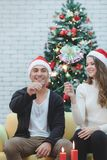 Youn par i den röda hatten som sitter på soffan mellan julträd a royaltyfria foton