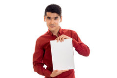 Youn stylish brunette male model in red shirt posing with empty placard in his hands and looking at the camera isolated Royalty Free Stock Photo