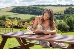 Yound可爱的妇女,读室外的书,享用咖啡 免版税库存图片