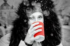 Yound女孩喝黑白一个红色的杯子热的茶 免版税图库摄影
