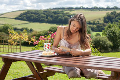 Yound attractive woman, reading a book outdoor, enjoying coffee Royalty Free Stock Images