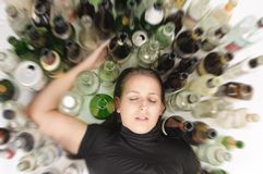 Yound beautiful woman in depression, drinking alcohol. Young woman in jeans and t-shirt sitting on the floor with lots of empty beer bottles and is drunk Royalty Free Stock Photos