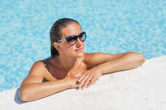 Yound beautiful woman rests at the pool. In summertime Royalty Free Stock Photos