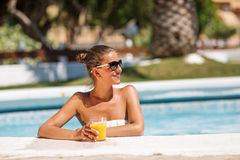 Yound beautiful woman rests at the pool. In summertime Stock Images
