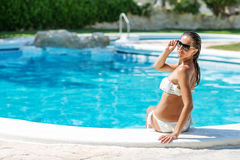 Yound beautiful woman rests at the pool. In summertime Royalty Free Stock Photo