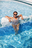 Yound beautiful woman rests at the pool. In summertime Stock Photography