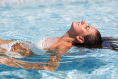 Yound beautiful woman rests at the pool. In summertime Stock Photo