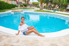 Yound beautiful woman rests at the pool in summertime.  Stock Photo