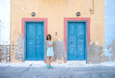 Yound blond woman at typical greek traditional town with colorful buildings on Kastelorizo Island, Greece Royalty Free Stock Image