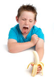 Yound boy not happy about eating a banana. Royalty Free Stock Photo