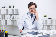 Yound doctor having telephone conversation Stock Images
