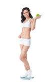 Yound fit girl standing on scales Stock Photography