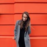 Yound-Frau auf der orange Wand Stockfotografie