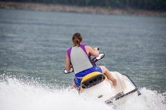 Yound-Frau, die einen Jet-Ski reitet Lizenzfreie Stockfotos