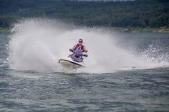 Yound-Frau, die einen Jet-Ski reitet Stockfoto