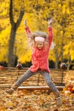 Yound girl jumping in autumn park Stock Image