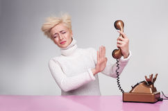 Angry handset. Yound lady trying to hold back the handset of an antique phone Stock Images