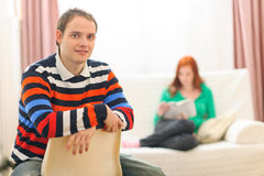 Yound man and girlfriend reading in background Royalty Free Stock Photo