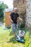 Yound man som mejar gräsmattan Royaltyfri Bild