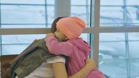 Yound mother and little cute daughter gently embrace at airport. Yound mother and little cute daughter gently embrace at airport while waiting flight at Royalty Free Stock Image