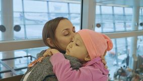 Yound mother and little cute daughter gently embrace at airport. Yound mother and little cute daughter gently embrace at airport while waiting flight at Royalty Free Stock Photos