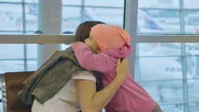 Yound mother and little cute daughter gently embrace at airport. Yound mother and little cute daughter gently embrace at airport while waiting flight at Stock Photos