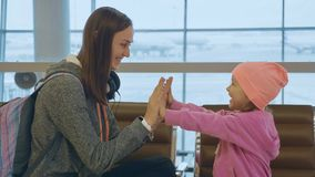 Yound mother and little cute daughter having fun at airport. Happy family plays pattycake game while waiting flight at departure lounge Stock Photo