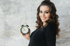 Yound pregnant woman hold a clock in her hands. Beautiful portrait of future mother. Woman waiting for a child, baby stock image