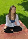 Yound pretty Russian Girl in lotus seat meditating Royalty Free Stock Image