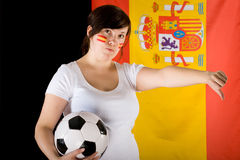 Yound sad, unhappy female football fan, thumb down. Young spain team supporter, thumb down, sad and unhappy, spanish flag as background, and spanish flags on her Stock Photos