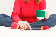 Yound woman with cup of coffee and touch pad at home Stock Photo