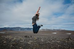 Yound woman jumping from joy on typical ring road view with empty road in the background without any cars in Iceland in summer,. Film effect royalty free stock image