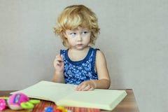Youndmeisje het schilderen tekening in album stock fotografie