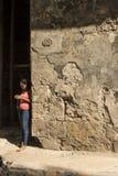 Youndvrouw die zich door versleten muur Havana bevinden Stock Afbeeldingen