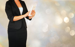 Younf elegant woman in buisiness suit holding tablet in front of glamourus bokeh lights background Royalty Free Stock Image