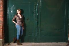 Younf Frau, die grüne Türen bereitsteht Stockbilder