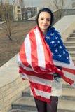 Younf latinokvinnor snedvred i USA-flagga utomhus royaltyfri foto