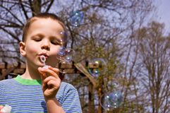 Young 4 Year Old Boy Blowing Bubbles. This young 4 year old boy is having a great time blowing bubbles outdoors Royalty Free Stock Images