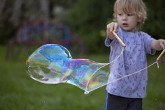 Free Young, 4 Year Old Preschool Boy With A Grey Shirt And Blond Hair, Blowing Bubbles In The Yard Stock Photography - 189363362