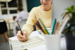 Circling data. Young accountant circling numbers in financial document with pencil while counting salary of office workers royalty free stock photos
