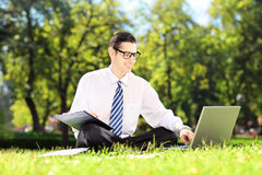 Young accountant seated on a grass working on a laptop and writi Stock Images