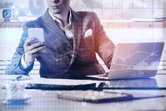 Young accountant at workplace. Young businessman using smartphone and laptop at modern workplace with abstract digital business pattern. Toned image. Accounting Stock Images