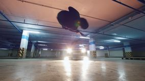 Young acrobat man athlet performs tricks at underground parking. Wide angle stock footage