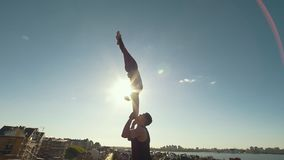 Young acrobatic couple performing flip, young man throws a woman in the air balancing on his arms at sunset outdoors. Slow motion stock footage
